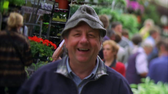 A man wearing a cap stands in an outdoor flower market. Available in HD.