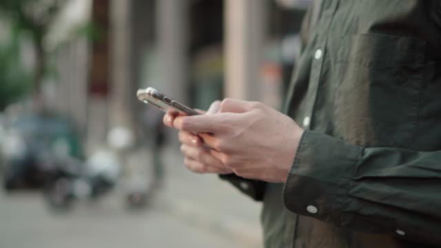 vidéos et rushes de un homme utilisant un masque facial et utilisant le smartphone sur la route - one man only