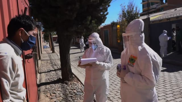 man wearing a face mask has his temperature taken as health personnel wearing ppe perform a questionnaire as they carry out a screening to detect... - la paz bolivia stock videos & royalty-free footage