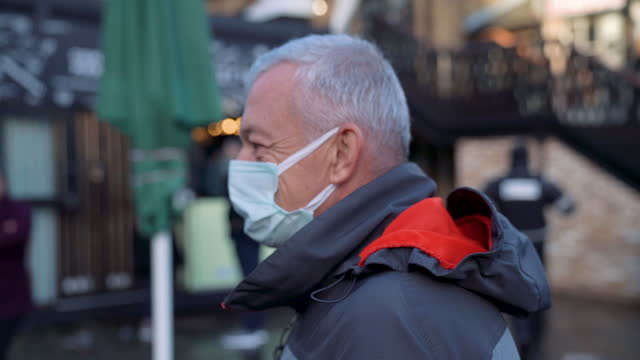 a man wearing a face mask in camden town bazaar - english culture stock videos & royalty-free footage