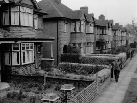 a man wearing a flat cap walks along a typical suburban street 1957 - doppelhaus stock-videos und b-roll-filmmaterial