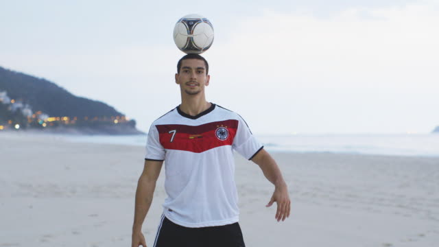 ms a man wearing a germany t-shirt practices his football skills on the beach / rio de janeiro, brazil - 2014 stock-videos und b-roll-filmmaterial