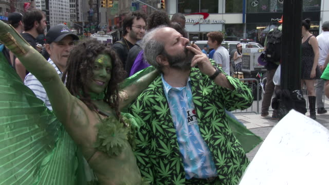 A man wearing a green Marijuana themed suit smokes a joint as he embraces a woman wearing green body paint and a cape in Union Square Park New York...