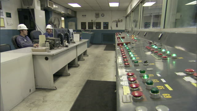 a man wearing a hard hat stands up in a control room to check a panel of lights and switches. - control room stock videos & royalty-free footage