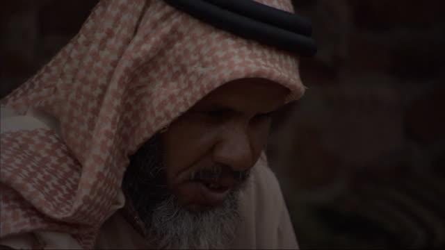 a man wearing a head scarf carries on a conversation. - ベドウィン族点の映像素材/bロール