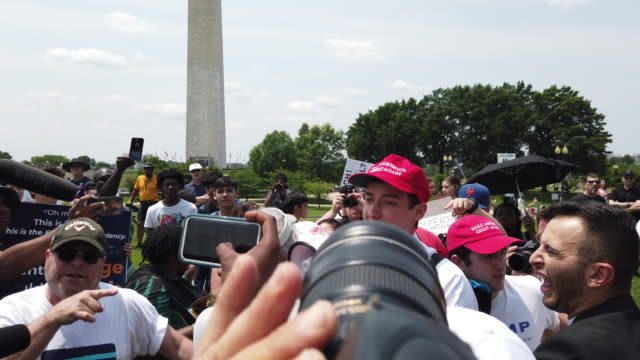 vídeos de stock, filmes e b-roll de a man wearing a make america great again hat who had been chanting build the wall on a megaphone during the impeach trump rally/march falls down... - stage make up