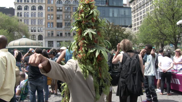 A man wearing a Marijuana Plant costume poses for pictures at the annual Cannabis Day Rally in Union Square New York