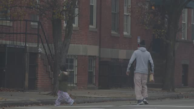vídeos de stock, filmes e b-roll de man wearing a mask crosses the street with his daughter on a foggy morning during the coronavirus pandemic on december 12, 2020 in baltimore,... - cruzar