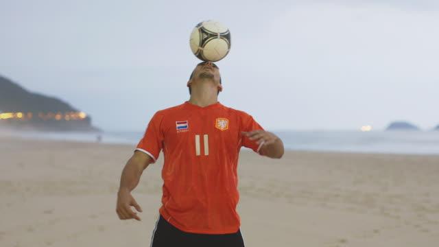 vídeos y material grabado en eventos de stock de ms a man wearing a netherlands t-shirt practices his football skills on the beach / rio de janeiro, brazil - perilla