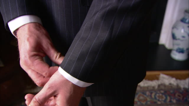 vídeos de stock e filmes b-roll de a man wearing a pinstripe suit adjusts his cuffs. - calçada