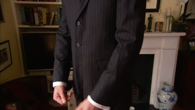 a man wearing a pinstripe suit and tie adjusts his clothing as he stands in a study. - pinstripe stock videos & royalty-free footage