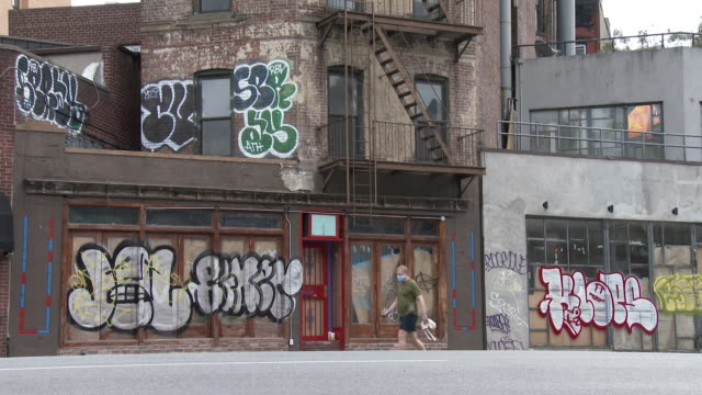 a man wearing a protective face mask walks past a row of shuttered businesses covered in graffiti on 7th avenue south on september 26 2020 in the... - scott mcpartland stock videos & royalty-free footage