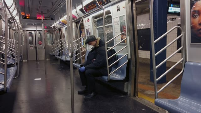 man wearing a protective mask and rubber gloves is seen on an empty subway car - major cities in the u.s. adjust to restrictive coronavirus measures... - new york city stock videos & royalty-free footage