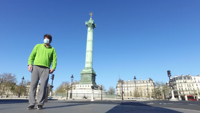 vídeos de stock, filmes e b-roll de a man wearing a protective mask is walking near place de la bastille in paris authorization for short trips within the limit of one hour daily and... - bastille