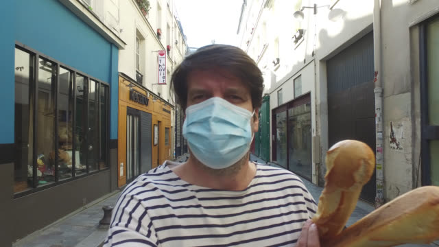 man wearing a protective mask walking on the street with baguette. it is permitted to make essential purchases in establishments whose activities... - one person stock videos & royalty-free footage