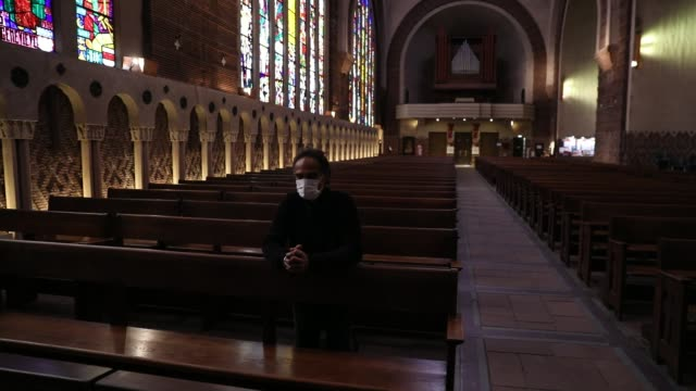 a man wearing a sanitary mask prays inside sainteodile church on march 29 2020 in paris france - 宗教施設点の映像素材/bロール