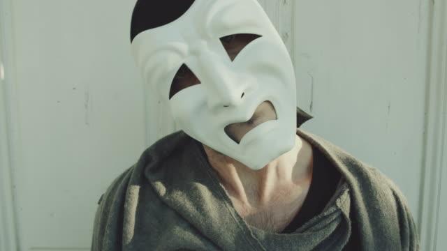 mann trägt eine furchterregende theatralische maske blick in die kamera und machen hand drohgebärden - computerhacker stock-videos und b-roll-filmmaterial