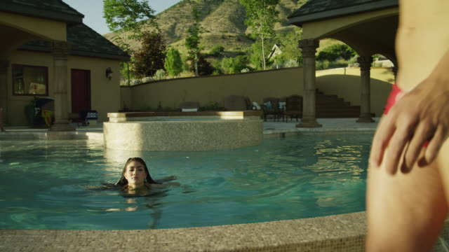 vídeos de stock, filmes e b-roll de ms man wearing a small swim suit  in front of woman at poolside / cedar hills, utah, usa - lago infinito