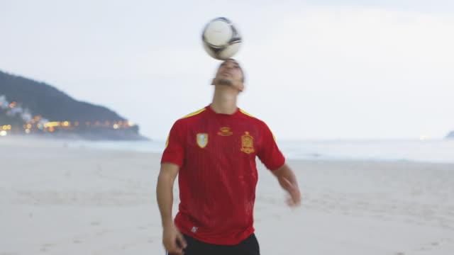 vídeos y material grabado en eventos de stock de ms a man wearing a spain t-shirt practices his football skills on the beach / rio de janeiro, brazil - perilla