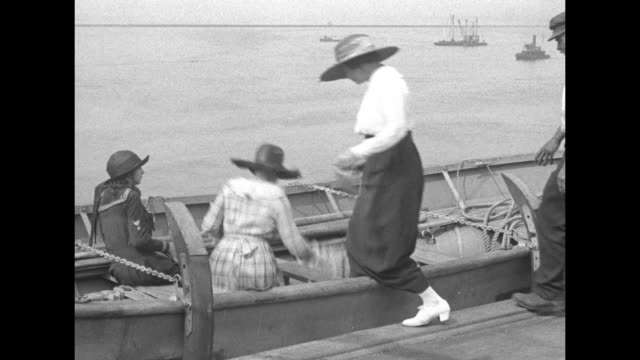vídeos de stock e filmes b-roll de a man wearing a straw boater affixes a curved device to the side of a lifeboat women a girl and crew members climb in / vs the boat is slowly lowered... - barco salva vidas