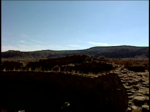 a man wearing a straw hat peers through a series of openings in wall of the great kiva at pueblo bonito in new mexico. - chaco canyon stock videos & royalty-free footage