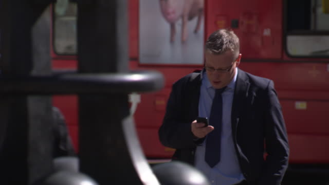 a man wearing a suit appears to find his bearings using his smart phone on a london street, uk. - confusion stock videos and b-roll footage