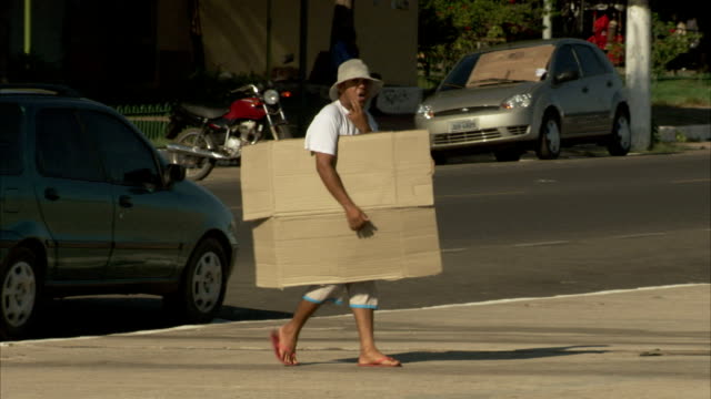 A man wearing a sunhat carries large pieces of cardboard across a city street in Santarem, Brazil. Available in HD.