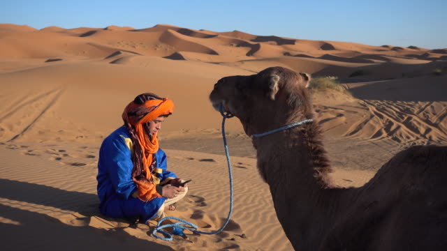 man wearing a traditional headscarf types on his smartphone in the desert - afrika stock-videos und b-roll-filmmaterial