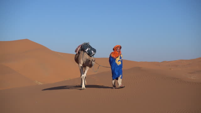 Man wearing a traditional shesh leads his cable through the desert