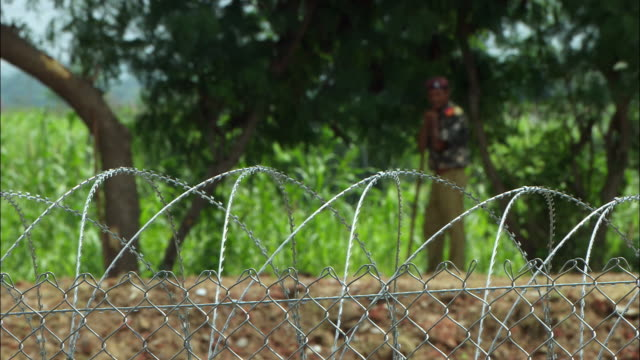 A man wearing a uniform stands behind a barbed wire fence. Available in HD.