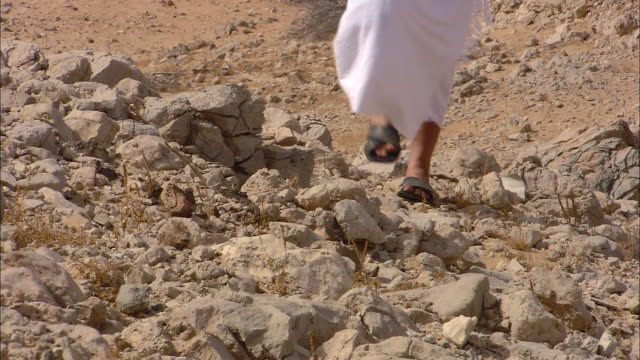 a man wearing a white robe and sandals walks over rocks in the desert. - land stock videos & royalty-free footage