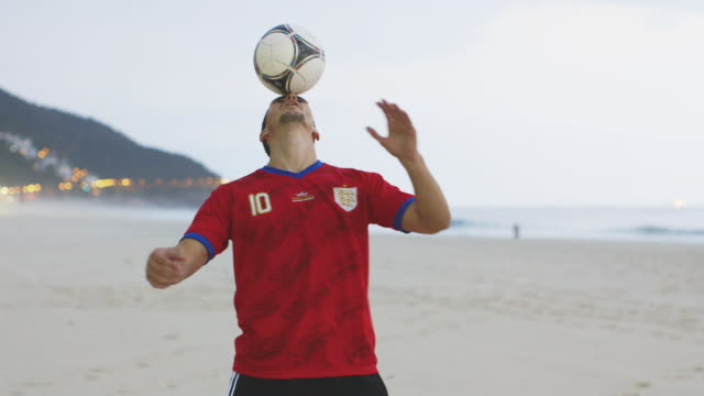 ms a man wearing an england t-shirt practices his football skills on the beach / rio de janeiro, brazil - balance stock videos & royalty-free footage