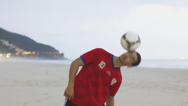 vídeos y material grabado en eventos de stock de ms a man wearing an england t-shirt practices his football skills on the beach / rio de janeiro, brazil - perilla