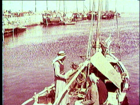 1965 reenactment montage man wearing arab-style white burnoose-headdress standing on boat in harbor port; two men sitting at bazaar market square with baskets of pearls for sale / middle east - headdress stock videos & royalty-free footage