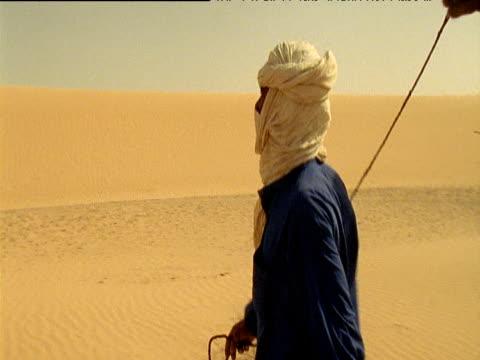 vidéos et rushes de man wearing blue robe and white turban leads camel train across sahara desert - coiffe traditionnelle
