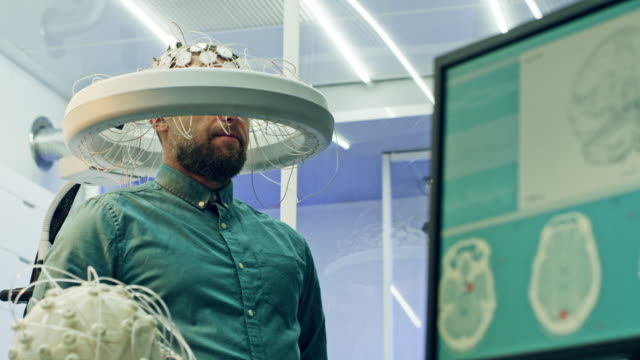 man wearing brainwave scanning headset. - human brain stock videos & royalty-free footage