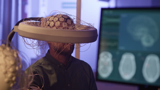 man wearing brainwave scanning headset. - neuroscience stock videos & royalty-free footage