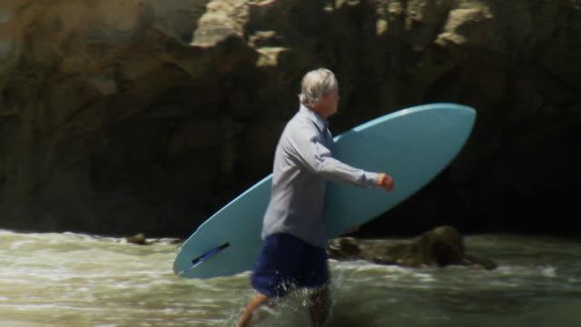 ms pan man wearing business shirt carrying surfboard walking along beach then paddling into sea on surfboard, laguna beach, california, usa - laguna beach california stock videos & royalty-free footage