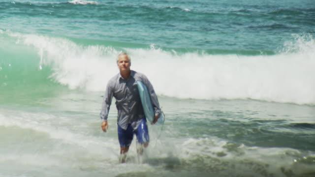 WS Man wearing business shirt carrying surfboard walking out of sea, Laguna Beach, California, USA