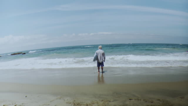 vidéos et rushes de ws man wearing business shirt standing in water with surfboard, laguna beach, california, usa - 50 54 ans