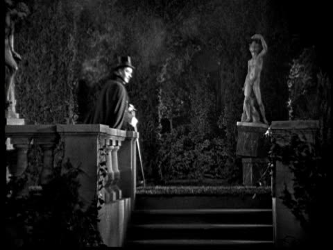1925 ms b/w man wearing cape and top hat walking in garden at night - anno 1925 video stock e b–roll