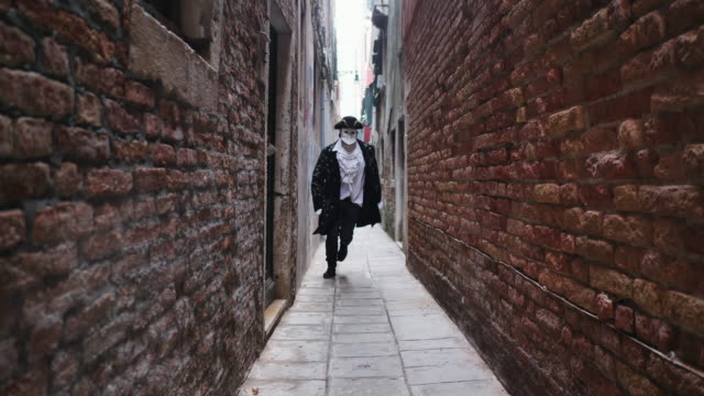 man wearing carnival costume and venetian mask jumping in narrow alley - fasching stock-videos und b-roll-filmmaterial