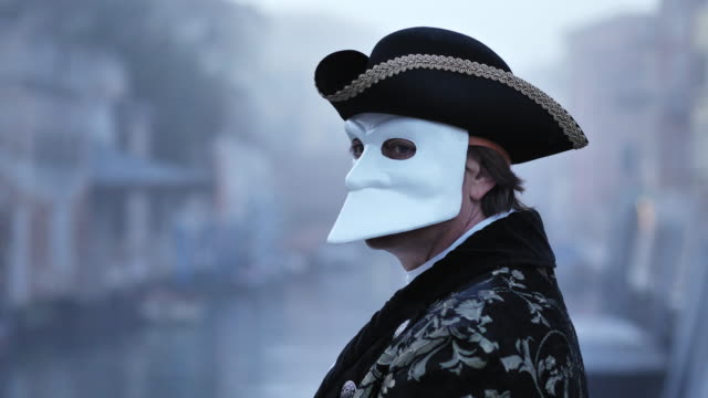 man wearing carnival costume and venetian mask standing outdoors on foggy day - verdecktes gesicht stock-videos und b-roll-filmmaterial