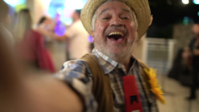 vidéos et rushes de homme portant le costume pour la partie de junina, prenant un selfie - chapeau