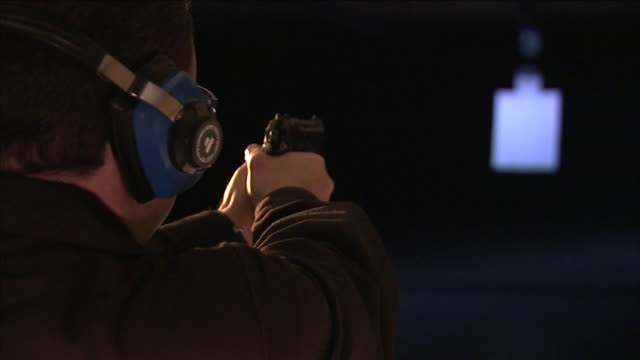 vidéos et rushes de a man wearing ear protection aims and fires a gun. - tir à l'arme à feu