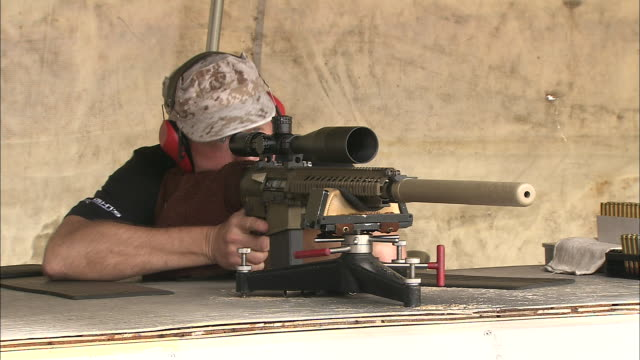 a man wearing ear protectors fires a rifle at a shooting range. - ear protectors stock videos and b-roll footage