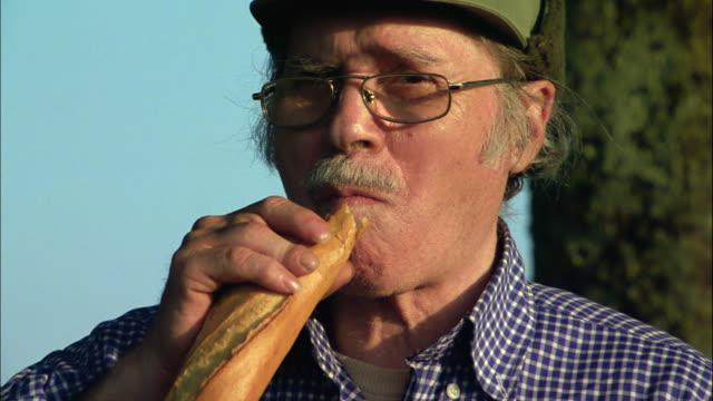 A man wearing eyeglasses eats a baguette.
