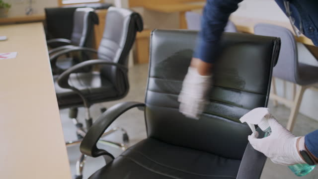 man wearing face mask and plastic glove using aerosol spray alcohol for cleaning office chair during covid-19 virus - cleaning stock videos & royalty-free footage