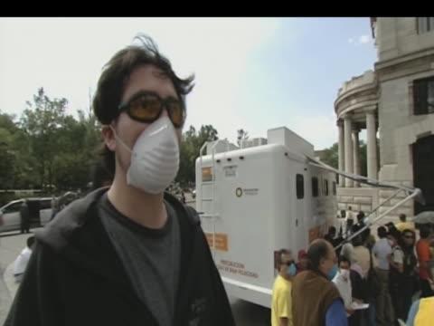 vídeos de stock, filmes e b-roll de man wearing face mask comments on fears of possible swine flu epidemic mexico 1 may 2009 - gripe suína