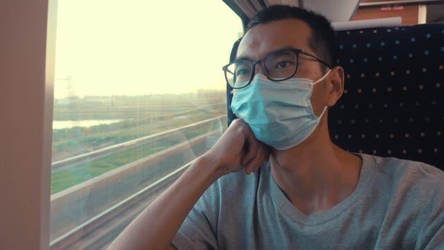 man wearing face mask travel in train because coronavirus - public transport stock videos & royalty-free footage